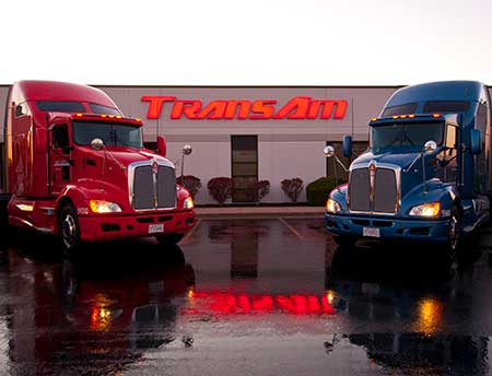 Red and blue truck outside the TransAm Trucking building